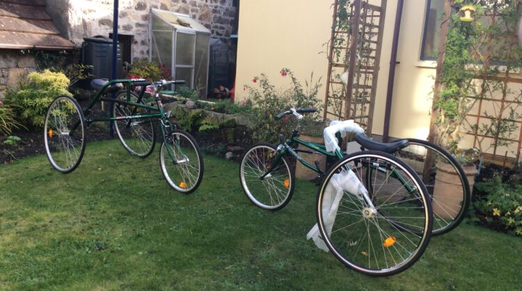 Two Racerunning bikes sat on grass on display facing each other