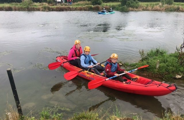 Three children in a kayak paddle between two banks in a pond.
